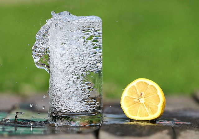 glass of water with a slice of lemon next to it